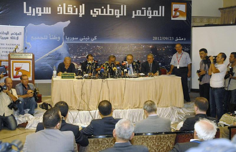 In this photo released by the Syrian official news agency SANA, Syrian opposition figures headed by the National Coordination Body for Democratic Change in Syria called for the overthrow of President Bashar Assad at a rare meeting of anti-regime groups in the government-controlled capital Damascus, Syria, Sunday, Sept. 23, 2012. The attendance of diplomats from Russia, Iran and China, all countries that support Assad, suggested the regime authorized the conference to bolster its own rhetoric that there should be a peaceful settlement to the Syrian crisis through dialog. (AP Photo/SANA)