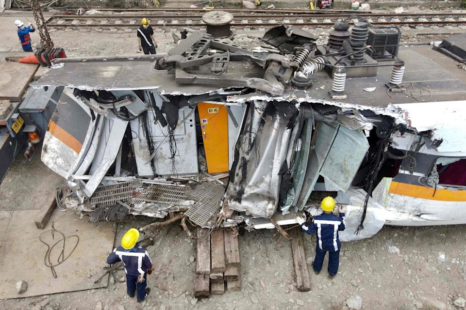 Workers inspect damaged train carriages at the site of the accident in Hualien on Tuesday. Photo: AFP