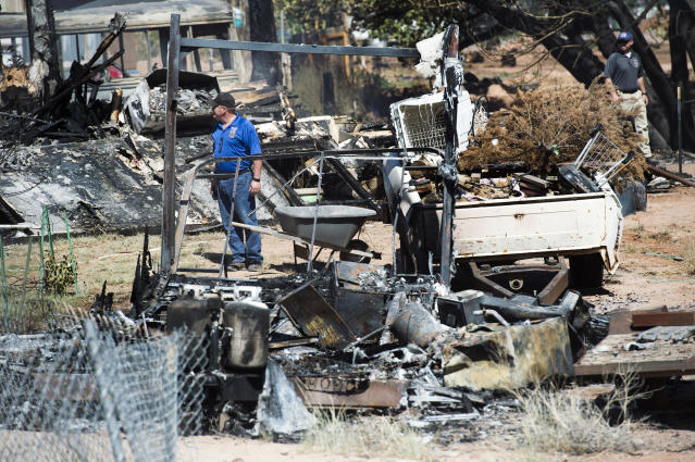 <p>Fire investigators walk among the property destroyed by the fire near Pack Creek, in Moab, Utah, Wednesday, June 13, 2018. (Photo: Rick Egan/The Salt Lake Tribune via AP) </p>