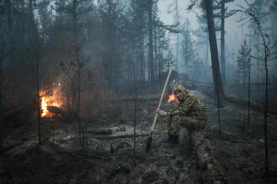 A member of volunteers crew rests as he mops up spot fires at Gorny Ulus area west of Yakutsk, Russia, Thursday, July 22, 2021. The hardest hit area is the Sakha Republic, also known as Yakutia, in the far northeast of Russia, about 5,000 kilometers (3,200 miles) from Moscow. Volunteers have joined over 5,000 regular firefighters in the effort, motivated by their love of the vast region. (AP Photo/Ivan Nikiforov)