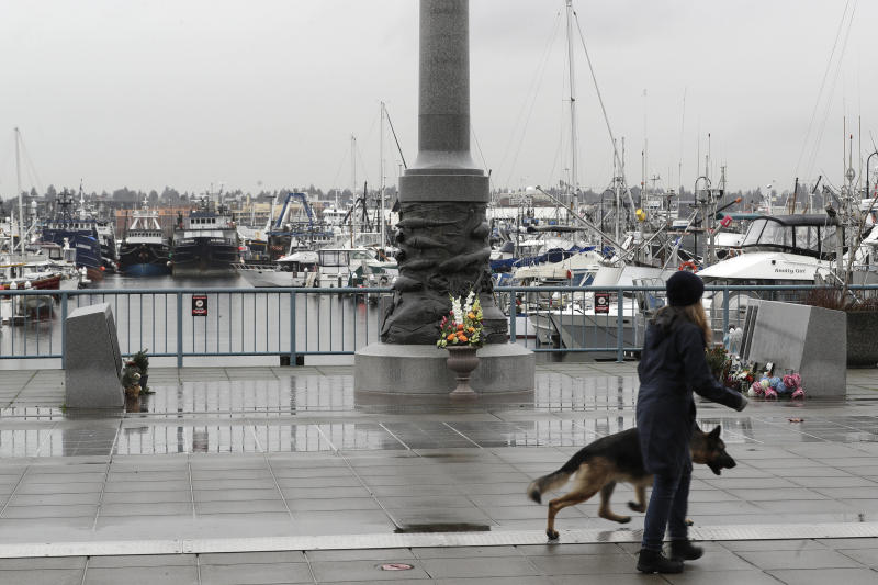 A pedestrian and a dog walk past the Seattle Fishermen's Memorial, Thursday, Jan. 2, 2020, in Seattle. Items left at the memorial Thursday included a ball cap with the name of the crab fishing boat Scandies Rose, a 130-foot crab fishing boat from Dutch Harbor, Alaska, that sank on New Year's Eve. (AP Photo/Ted S. Warren)