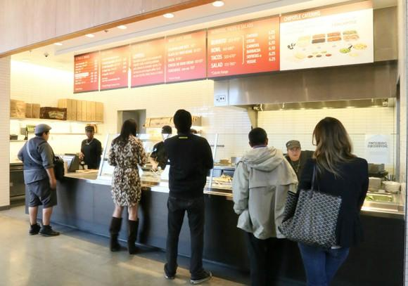 Customers stand in line at a Chipotle.