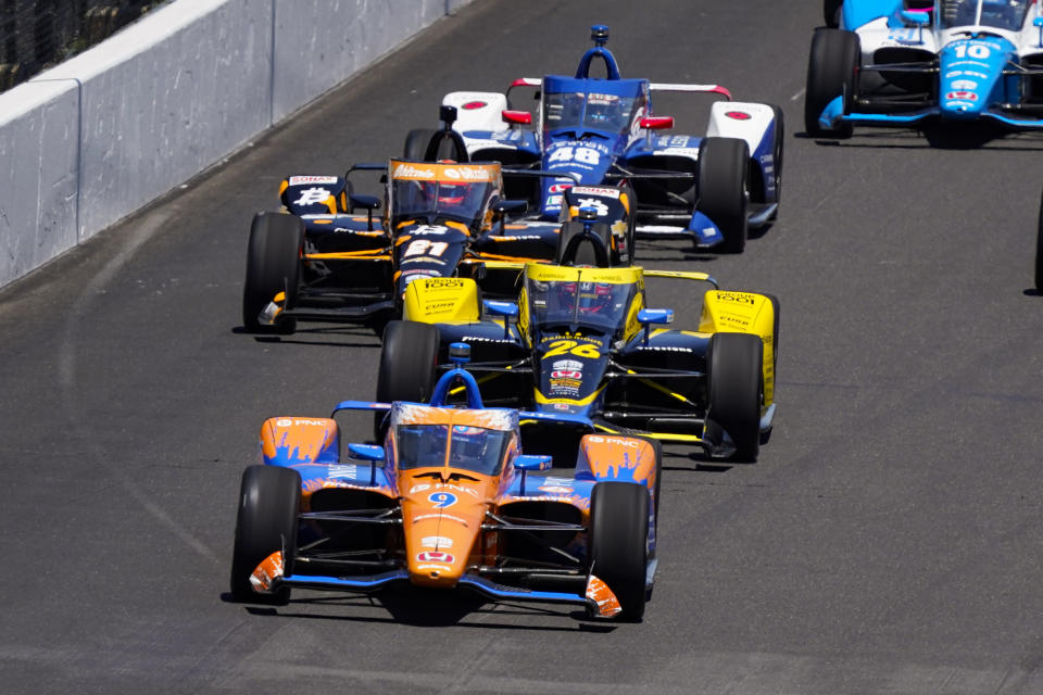 Scott Dixon, of New Zealand, leads the field into the first turn at the start the Indianapolis 500 auto race at Indianapolis Motor Speedway in Indianapolis, Sunday, May 30, 2021. (AP Photo/Paul Sancya)