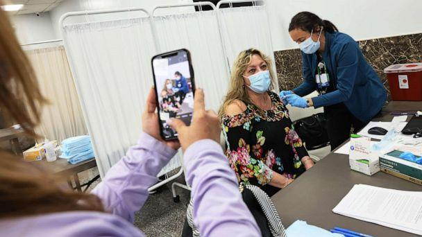 PHOTO: Mara Bianco takes a photo of Dawn Casale as she receives the Johnson & Johnson COVID-19 vaccine at the Northwell Health pop-up vaccination site at the Albanian Islamic Cultural Center in Staten Island on April 08, 2021, in New York City. (Michael M. Santiago/Getty Images)