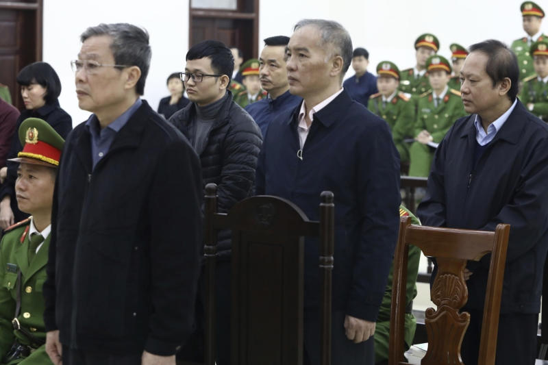 Vietnamese former Minister of information and communication Nguyen Bac Son, left, valuer Hoang Duy Quang, second left, former Mobifone Chairman Le Nam Tra, second right, former Minister of information and communication Truong Minh Tuan, right, stand as judge reads the verdicts at their trial in Hanoi, Vietnam Saturday, Dec. 28, 2019. Hanoi court on Saturday sentenced Son to life imprisonment in a multi-million dollar corruption case that also saw another minister and a dozen executives receive lengthy prison terms. (Nguyen Van Diep/VNA via AP)
