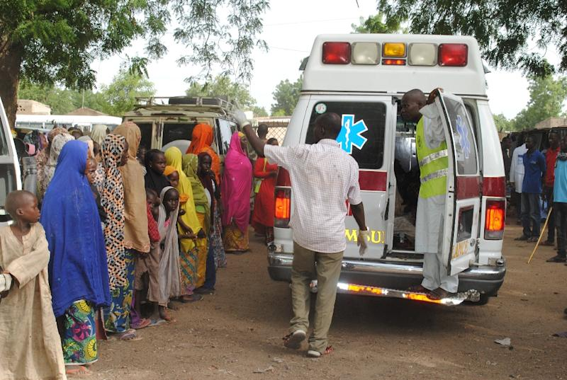 This photo taken on June 30, 2016 shows displaced children L) watching, as malnurished and sick children are being taken away in an ambulance for treatment in Bama's camp for internally displaced people (AFP Photo/Stringer)