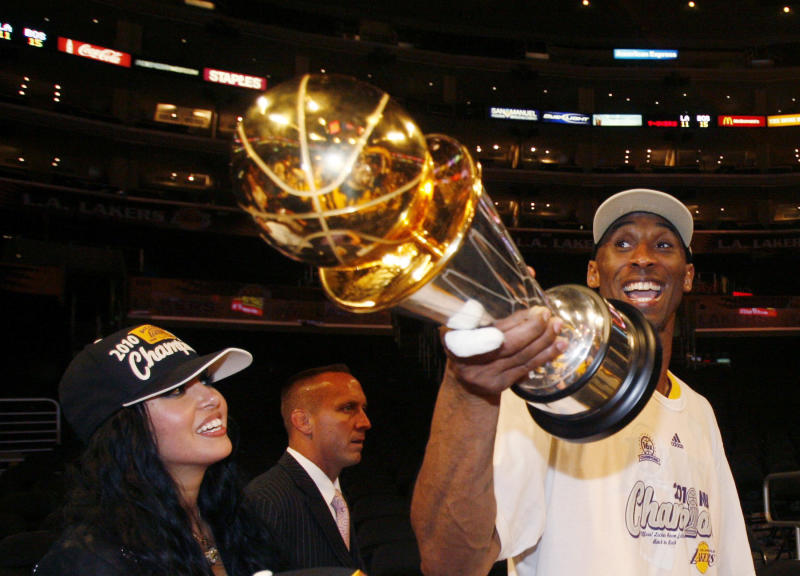 Los Angeles Lakers Kobe Bryant holds the NBA MVP trophy as he walks with his wife Vanessa after defeating the Boston Celtics to win Game 7 of the 2010 NBA Finals basketball series in Los Angeles, California, June 17, 2010. REUTERS/Lucy Nicholson (UNITED STATES - Tags: SPORT BASKETBALL)