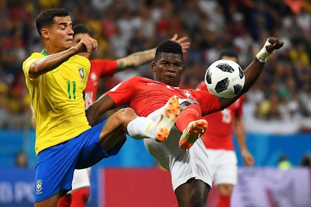 Philippe Coutinho battling for possession in Brazil's opening World Cup game against Switzerland (AFP Photo/JOE KLAMAR)