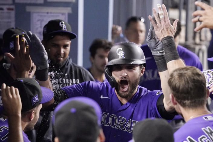 Colorado Rockies' Sam Hilliard is congratulated by teammates in the dugout after hitting a solo home run during the ninth inning of a baseball game against the Los Angeles Dodgers Friday, July 23, 2021, in Los Angeles. (AP Photo/Mark J. Terrill)
