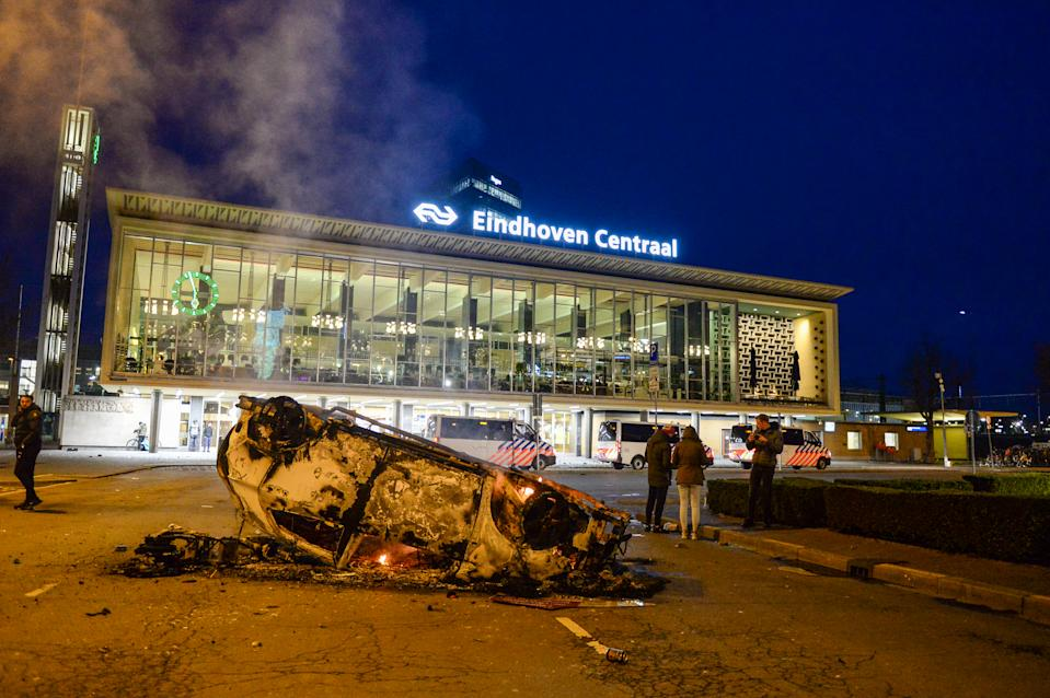 EINDHOVEN, NETHERLANDS - JANUARY 24: A car that has been turned over and set ablaze is seen near Eindhoven Central Station on January 24, 2021 in Eindhoven, Netherlands after a forbidden protest against the coronavirus measures turned into riots. Police cleared the area in and around Central Staition after rioters looted a supermarket and set fire to a car. (Photo by Joris Verwijst/BSR Agency/Getty Images)
