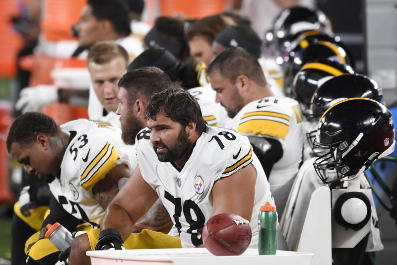 Alejandro Villanueva in a No. 78 jersey sits with teammates on the bench.