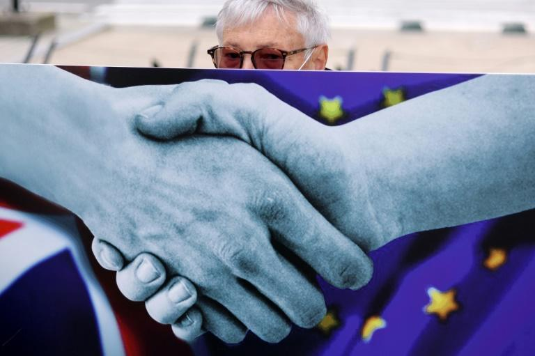 An anti-Brexit activist holds a placard to protest near the European Council Building prior to a two-day European Union (EU) summit in Brussels, on October 15, 2020