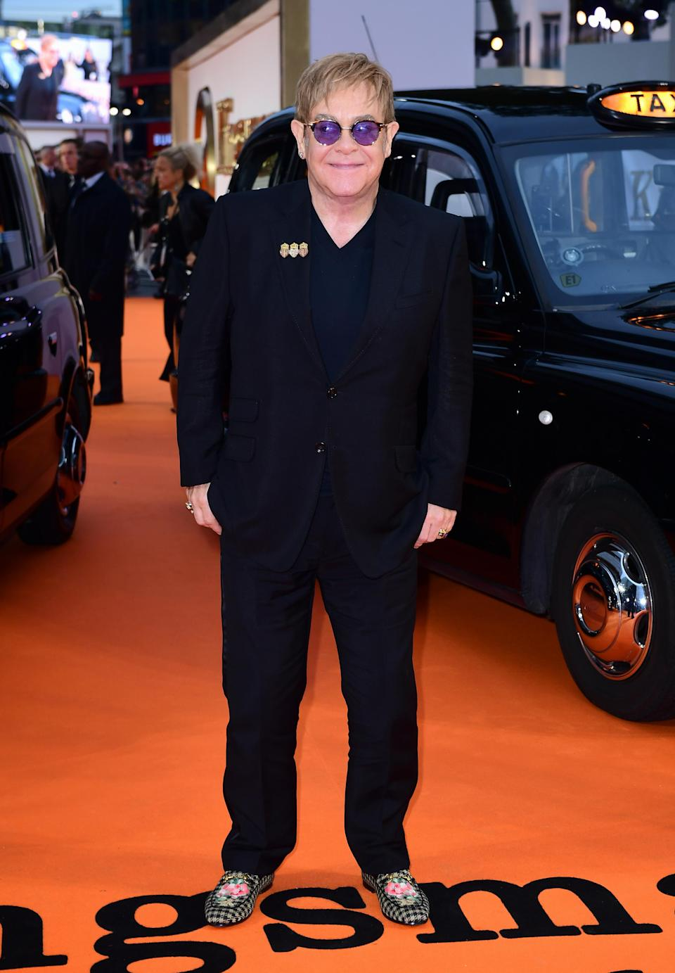 <p>Elton arrived in a traditional black suit, accessorising with a pair of printed smoking slippers and his signature sunglasses.<br><i>[Photo: PA]</i> </p>