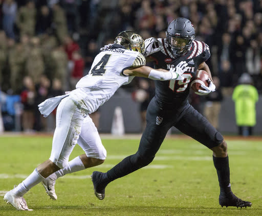 North Carolina State's C.J. Riley (19) carries the ball as Wake Forest's Amari Henderson (4) attempts a tackle during the first half of an NCAA college football game in Raleigh, N.C., Thursday, Nov. 8, 2018. (AP Photo/Ben McKeown)