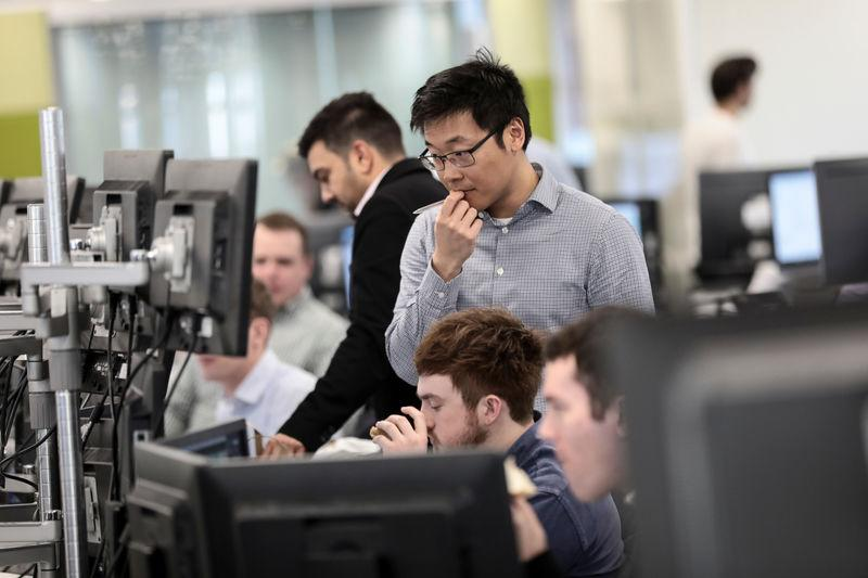 FILE PHOTO: Traders looks at financial information on computer screens on the IG Index trading floor in London, Britain February 6, 2018. REUTERS/Simon Dawson