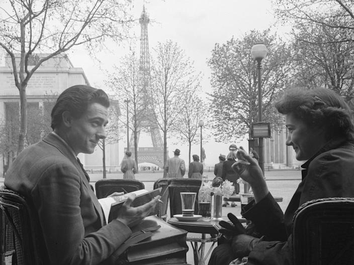 A couple smile at one another as they sit together at an outdoor cafe in sight of the Eiffel Tower, Paris, France, April 1950.