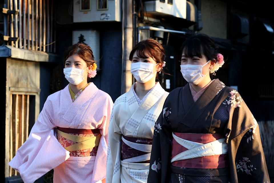 KYOTO, JAPAN - MARCH 06: Women dressed in Kimono costume as wearing a face mask walk on March 06, 2020 in Kyoto, Japan. The tourism industry in Japan as seen a decline in recent weeks with the concern over the spread of Coronaviros (COVID-19) on the rise and travel restrictions in place. Prime Minister Shinzo Abe last week recommended the cancellation of large-scale sport and cultural events and there is speculation the Olympics may be postponed or cancelled if the situation does not improve. (Photo by Buddhika Weerasinghe/Getty Images)