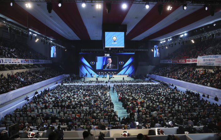 Turkey's President Recep Tayyip Erdogan is seen on a screen as he delivers a speech at his ruling party's congress inside a packed sports hall in Ankara, Turkey, Wednesday, March 24, 2021. Erdogan has come in the firing line for holding the rally inside the closed venue amid a new surge in COVID-19 cases. Thousands of party supporters filled the stands of the 10,400-capacity sports hall in the capital, in disregard of the government's own social distancing rules to fight the coronavirus pandemic. (Turkish Presidency via AP, Pool)