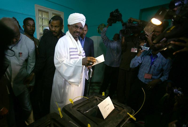 Sudanese President Omar al-Bashir (C) casts his vote in the presidential elections at a polling station in the Saint Francis school in the capital, Khartoum, on April 13, 2015 (AFP Photo/Ashraf Shazly)