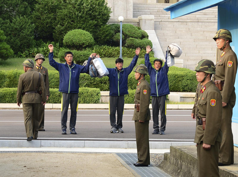 In this photo released by South Korea's Unification Ministry, North Koreans cheer after returning from South Korea at the border village of Panmunjom, South Korea, Friday, July 6, 2013. South Korea repatriated three North Koreans rescued in South Korean waters aboard their drifting boat. (AP Photo/Unification Ministry)