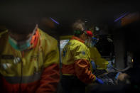 Paramedics tend to a patient who doesn't have COVID-19 inside an ambulance in Barcelona, Spain, April 6, 2020. Medical crews have been doing extra duty during the coronavirus pandemic, checking on patients who are positive and not. (AP Photo/Emilio Morenatti)