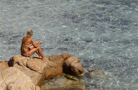 """A woman sits by the rocks at the Ramizzo beach in the so called """"Emerald Coast"""" of the Sardinia island"""