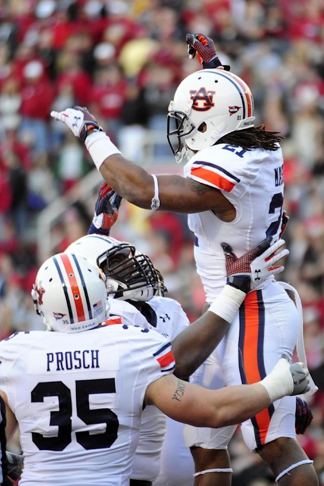 Auburn offensive linesman Avery Young, center, holds teammate running back Tre Mason as they are joined by fullback Jay Prosch celebrating Mason's first half touchdown is an NCAA college football game against Arkansas in Fayetteville, Ark., Saturday, Nov. 2, 2013. (AP Photo/Beth Hall)