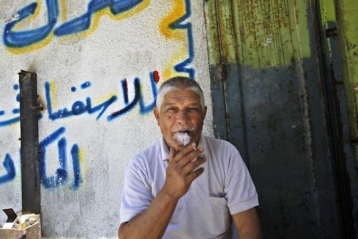 In this Wednesday, June 19, 2013 photo, Foud Al Hamami, 67, a Palestinian Muslim Sunni, speaks as he sits in front of his store at the Shati refugee camp in Gaza City.Hatreds between Shiites and Sunnis are now more virulent than ever in the Arab world because of Syria's brutal civil war. Hard-line clerics and politicians on both sides have added fuel, depicting the fight as essentially a war of survival for their sect. (AP Photo/Adel Hana)
