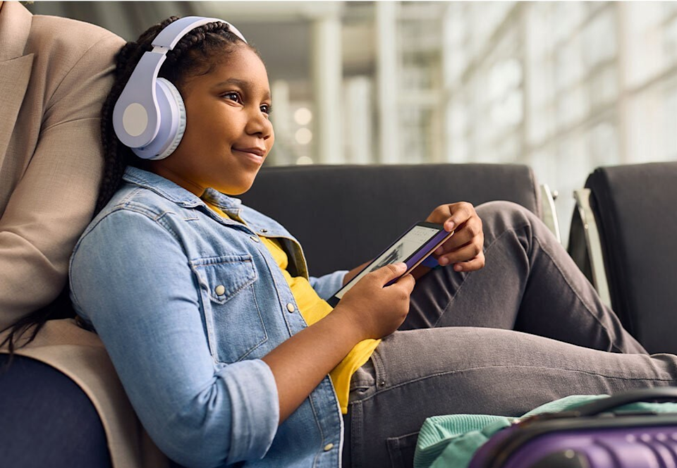 A child wearing headphones listens to an audiobook using a Kindle Paperwhite Kids e-reader,