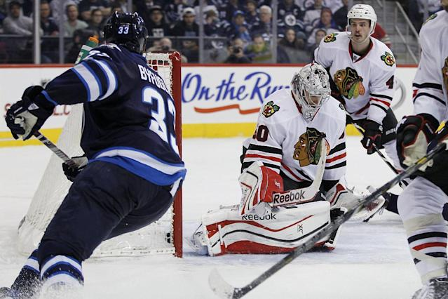 Winnipeg Jets' Dustin Byfuglien's (33) shot drops in behind Chicago Blackhawks goaltender Corey Crawford, second from left, for a goal during the second period of an NHL hockey game in Winnipeg, Manitoba on Thursday, Nov. 21, 2013. (AP Photo/The Canadian Press, John Woods)