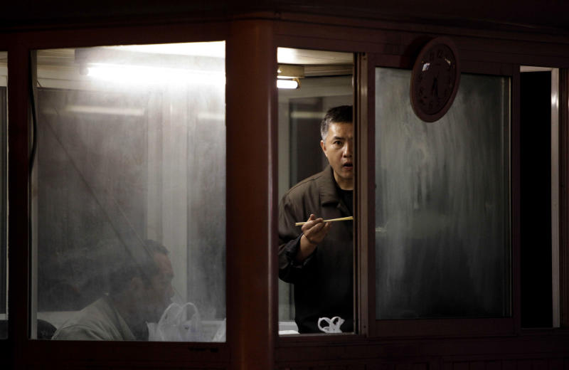 Security personnel eat their meals as they watch over a entrance to the residential compound where Liu Xia, the wife of this year's Nobel Peace Prize winner Liu Xiaobo, is being held under house arrest in Beijing on Monday, Oct. 11, 2010. Liu Xia confirmed in a Twitter message that she had been placed under house arrest since Friday. (AP Photo/Ng Han Guan)