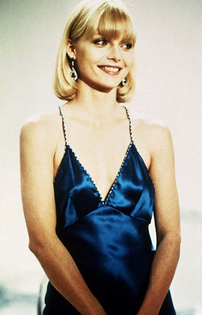 <p>Michelle Pfeiffer exudes glamour wearing various Halston-esque dresses while playing Elvira Hancock in <em>Scarface</em>. Her slinky, plunging-neckline teal evening gown is no exception. Designed by Patricia Norris, the minimalist look has served as inspiration for many fashion moments since the film premiered in 1983. </p>