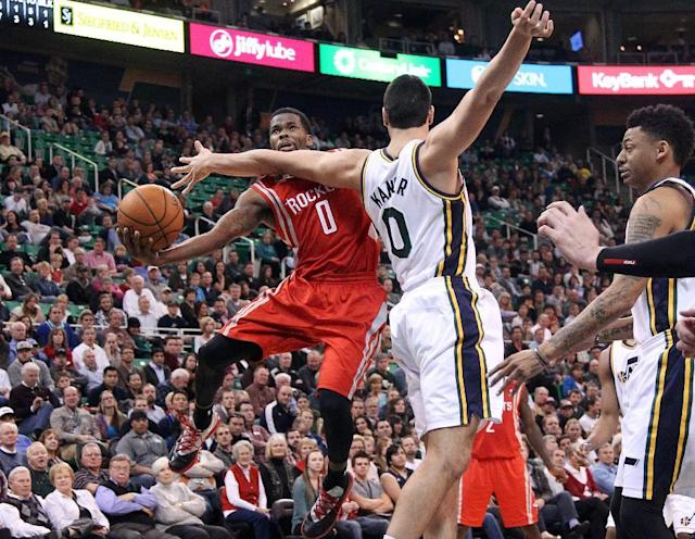 Houston Rockets' Aaron Brooks, left, goes to the basket as Utah Jazz's Enes Kanter (0) defends in the second quarter of an NBA basketball game Monday, Dec. 2, 2013, in Salt Lake City. (AP Photo/Rick Bowmer)