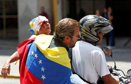 An opposition supporter is helped after being injured by a tear-gas canister in a rally against Venezuela's President Nicolas Maduro in Caracas. REUTERS/Christian Veron