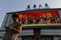 An electronic billboard featuring a new generation of revolutionary soldiers is seen near a shopping mall in Beijing