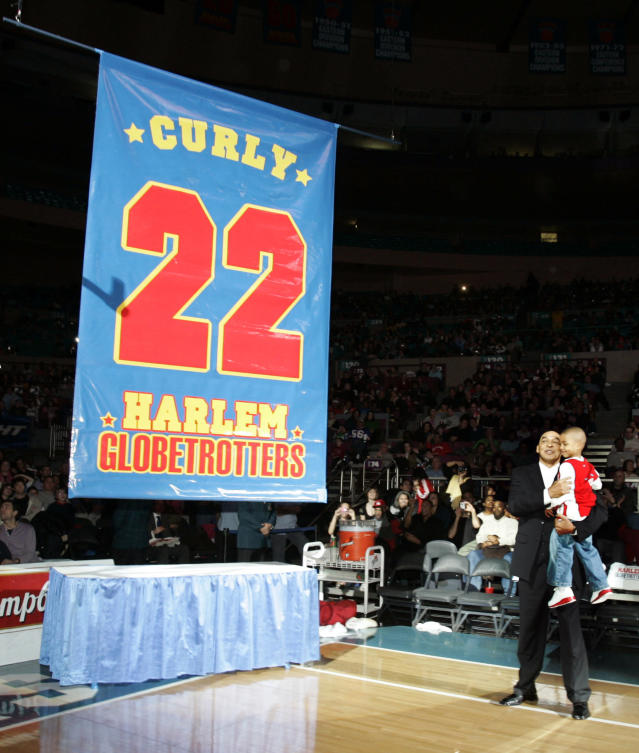 """FILE - In this Feb. 15, 2008, file photo, Harlem Globetrotters' Fred """"Curly"""" Neal looks on with his grandson Jaden Neal-Roberts as his No. 22 is retired by the world renowned Harlem Globetrotters at Madison Square Garden in New York. Neal, the dribbling wizard who entertained millions with the Harlem Globetrotters for parts of three decades, has died the Globetrotters announced Thursday, March 26, 2020. He was 77. Neal played for the Globetrotters from 1963-85, appearing in more than 6,000 games in 97 countries for the exhibition team known for its combination of comedy and athleticism. (AP Photo/Frank Franklin II, File)"""