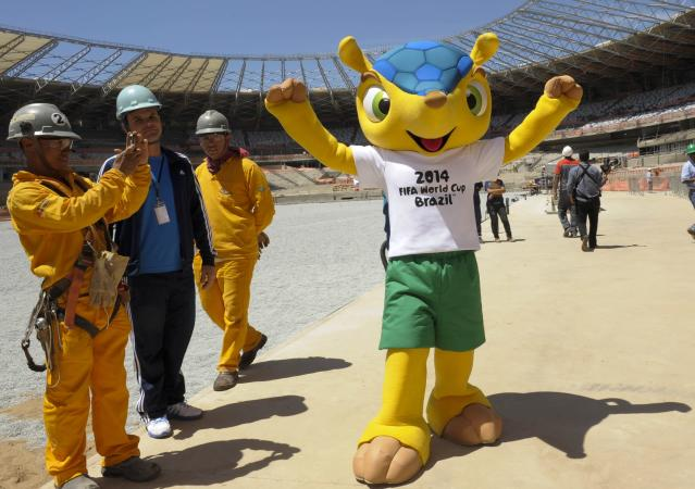 A workers takes pictures of the armadillo, the mascot for the 2014 World Cup, during a visit by FIFA's secretary-general Jerome Valcke to the Magalhaes Pinto stadium, know as Mineirao, in Belo Horizonte, Brazil, on October 16, 2012. Less than two years before the 2014 World Cup kicks off in Brazil, half of the 12 host stadiums are at least 50 percent completed -- being renovation or construction. AFP PHOTO/LIGHT PRESS/GUALTER NAVESGUALTER NAVES/AFP/Getty Images