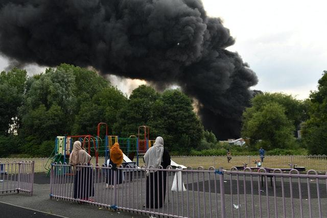 People watch on as smoke billows from a severe blaze on an industrial estate in Birmingham