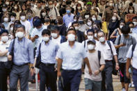 People wearing face masks to help curb the spread of the new coronavirus walk across a street in Osaka, Japan, Wednesday, July 29, 2020. As Japan battles a surge in coronavirus cases, some areas may be running out of isolation facilities to monitor infected people.(Kyodo News via AP)