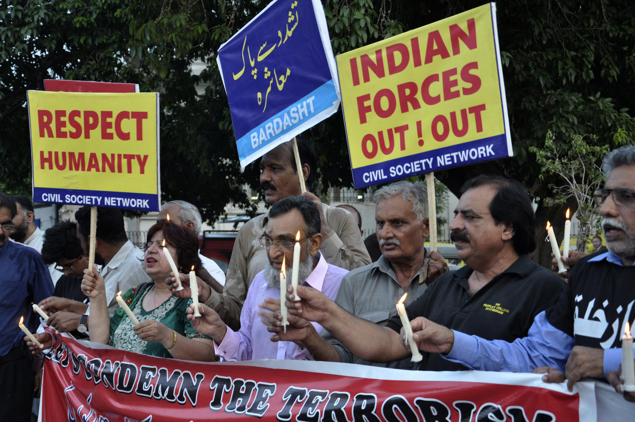 "Activists of the Civil Society Network rally to condemn recent attacks on elections rallies that killed dozens of people, and ongoing violence against Kashmiris by security forces in Indian Kashmir, in Lahore, Pakistan, Tuesday, July 17, 2018. Placard in center reads ""Violence free society."" (AP Photo/K.M. Chaudary)"
