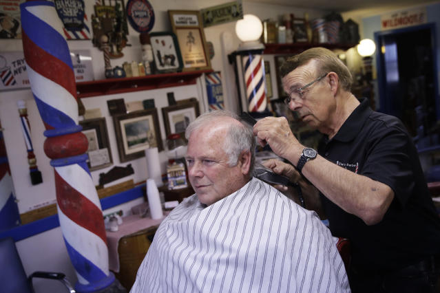 Stan Morin gives a haircut to Jeff McGee at his barber shop, Thursday, May 21, 2020, in Plainville, Kan. Morin said he has been two to three times busier than normal after reopening a week earlier following a 2-month closure in an effort to stem the spread of the coronavirus. (AP Photo/Charlie Riedel)