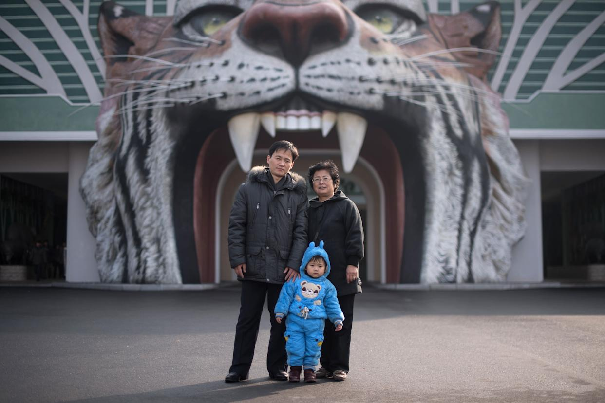 Toddler Mun Ji-Song poses for a photo with his parents at the entrance to the Central Zoo in Pyongyang.