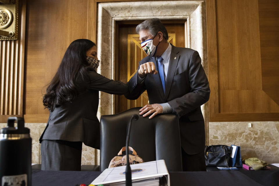 Sen. Joe Manchin, D-W.Va., greets Rep. Deb Haaland, D-N.M., before the start of the Senate Committee on Energy and Natural Resources hearing on her nomination to be Interior Secretary, Tuesday, Feb. 23, 2021 on Capitol Hill in Washington. (Graeme Jennings/Pool via AP)