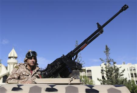 A member of the Libyan army guards the streets following yesterday's clashes in Benghazi