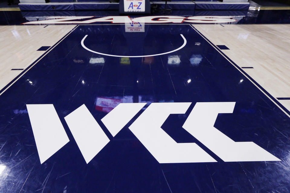 FILE- In this Nov. 5, 2019, file photo, the West Coast Conference logo is displayed at the court of the McCarthey Athletic Center before an NCAA college basketball game between Gonzaga and Alabama State in Spokane, Wash. 30 college conferences are still planning to hold basketball tournaments where the winner earns the automatic bid to the NCAAs. But the leagues also have until Feb. 26, 2021, to notify the selection committee if there will be any changes to how the automatic bid is awarded. (AP Photo/Young Kwak, File)