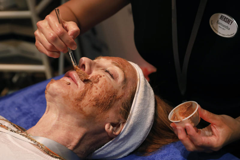 In this Tuesday, Aug. 6, 2019, photo, Hershey lead massage therapist Samantha Fisher applies a mini chocolate-and-marshmallow whip hydrating facial, at the 2019 International Spa Association event, in New York. It is Circadia's collaboration with MeltSpa by Hershey. (AP Photo/Richard Drew)
