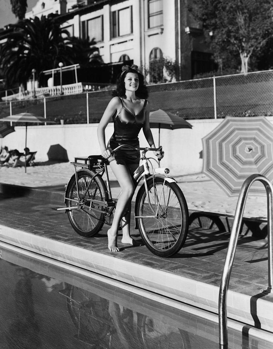 <p>Actress Rita Hayworth in a swimsuit by the side of a swimming pool at the Beverly Hills Hotel, California.</p><p>Other celebrity visitors this year: Norma Shearer, actor and dancer George Raft.</p>