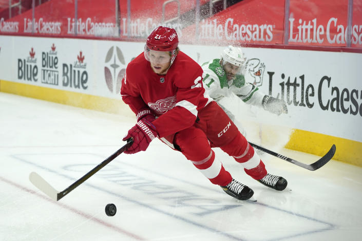 Detroit Red Wings defenseman Dennis Cholowski (21) protects the puck from Dallas Stars center Andrew Cogliano (11) in the first period of an NHL hockey game Thursday, April 22, 2021, in Detroit. (AP Photo/Paul Sancya)