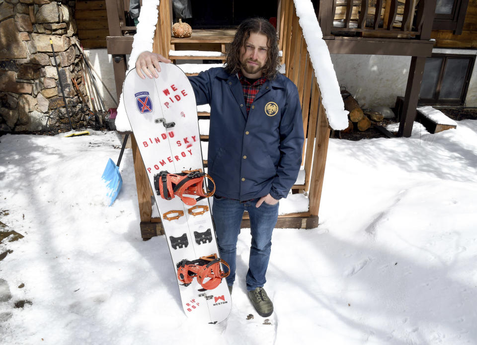 FILE - In this March 22, 2021, file photo, Evan Hannibal poses for a portrait outside his home in Vail, Colo. Prosecutors have dropped their bid for $168,000 in damages from two snowboarders who triggered a slide that buried a service road and destroyed an expensive avalanche mitigation system in Colorado's backcountry. Tyler DeWitt and Evan Hannibal, who are scheduled to appear in court June 7, each will instead plead guilty to a misdemeanor charge of reckless endangerment, defense attorney Jason Flores-Williams said Tuesday, May 18, 2021. (AP Photo/Thomas Peipert, File)