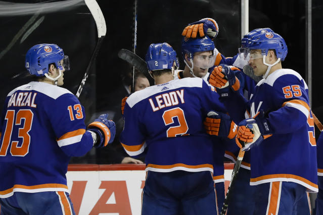 New York Islanders' Mathew Barzal (13), Nick Leddy (2) and Johnny Boychuk (55) celebrate with Brock Nelson after Nelson scored the game winning goal during the overtime period of an NHL hockey game against the Pittsburgh Penguins Thursday, Nov. 21, 2019, in New York. The Islanders won 4-3. (AP Photo/Frank Franklin II)